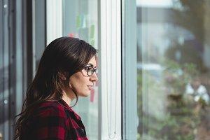 Thoughtful woman looking through window while having coffee
