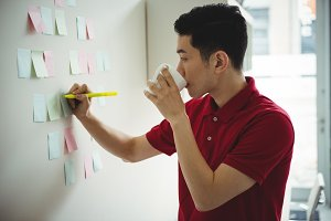Business executive writing on sticky notes while having cup of coffee