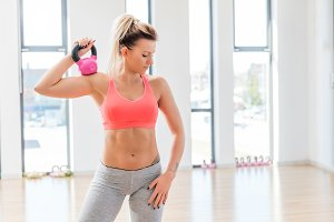 Fit woman holding a kettlebell after finished workout.
