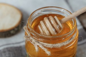 Glass pot of honey on a rustic bacground.