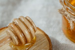 Close-up of honey dipper on a wood.