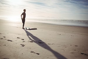 Man with surfboard exercising on beach