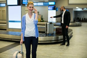 Businesswoman standing with luggage talking on mobile phone in waiting area