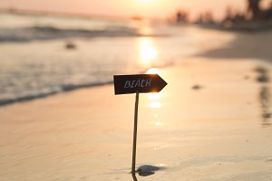 Vacation holidays idea - beach sign and sunset