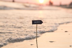 Summer holidays idea - beach sign and sunset