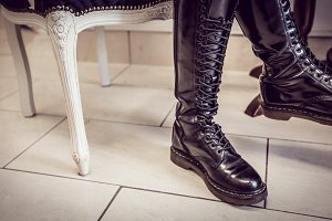 Female shop owner in long boot sitting in salon