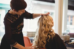 Female hairdresser styling clients hair