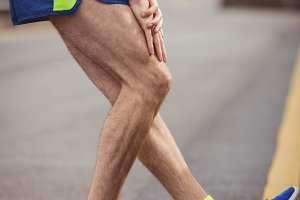 Man stretching his leg on the road