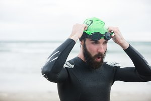 Athlete wearing swimming goggles on the beach