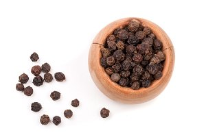 Black peppercorn in a wooden bowl isolated on white background. Top view