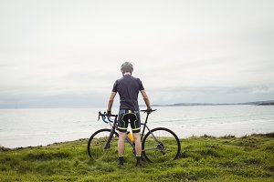 Athlete standing with his bicycle on grass