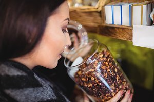 Close-up of beautiful woman smelling a jar of spice