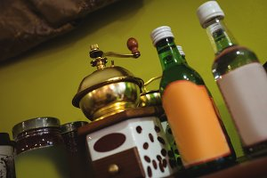 Close-up of coffee grinder and syrup bottles arranged on shelf