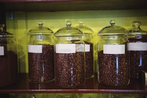 Close-up of jar of coffee beans arranged on shelf