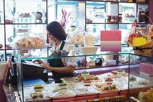 Female shopkeeper using cash register