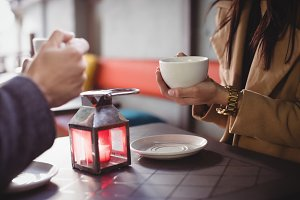 Couple holding coffee cups in restaurant