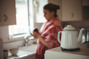 Kettle on the stove and woman standing in background