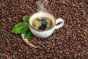 Black coffee with green leaves beans