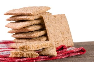 stack of crisp bread on a wooden table isolated white background