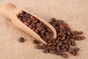 Coffee beans in a wooden scoop on sackcloth