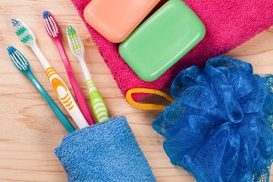 Toothbrushes, soap, sponge, towel on a wooden table. hygiene products. Top view