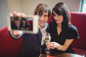 Couple holding drink and taking a selfie