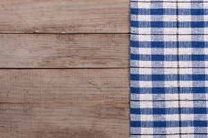 blue checkered tablecloth on an old wooden table with copy space for your text. Top view