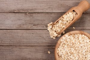 Oat flakes in a wooden bowl with a scoop on old wooden background with copy space for your text. Top view