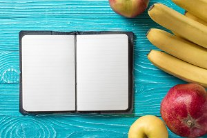 Notepad surrounded by fruit
