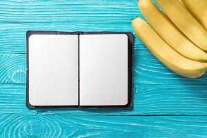Notebook next to bananas