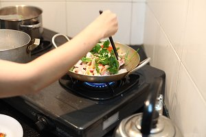 Happy housewife cooking squid with seafood in home kitchen