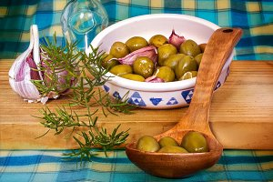 Green olives on a wooden spoon,