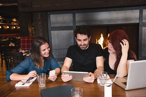Friends using digital tablet in bar