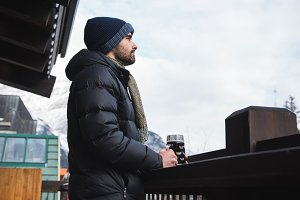 Man in winter clothing holding beer glass
