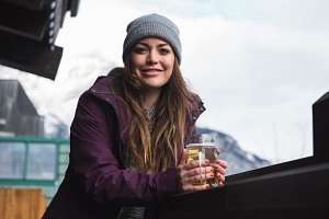 Woman in winter clothing holding beer glass