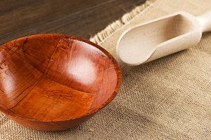 Wooden bowl and spoon on brown cloth. Horizontal shoot.
