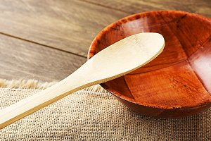 Wooden bowl and spoon on brown cloth.