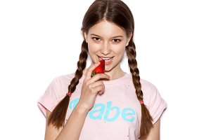 girl biting ripe strawberry