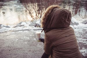 Woman sitting on river bank in winter