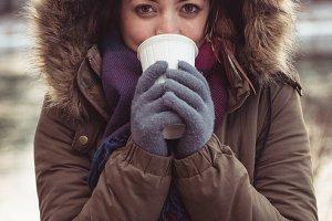 Beautiful woman in fur coat drinking coffee in winter