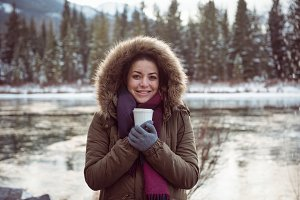 Beautiful woman in fur coat holding coffee cup in winter