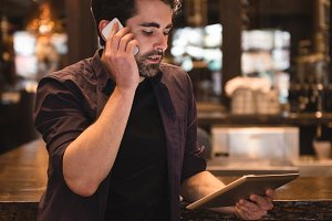 Man talking on mobile phone at bar counter