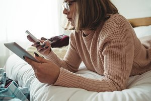 Woman lying on bed using mobile phone and digital tablet