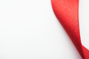 Background of red fabric ribbon. Isolated. Copy space.