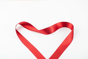 Abstract heart with red fabric ribbon. Isolated. Copy space.