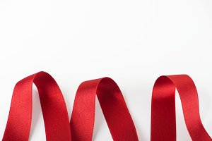 Abstract shapes background with red fabric ribbon on white background. Copy space.