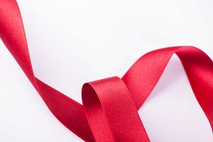 Abstract background of red fabric ribbon on white background. Copy space.