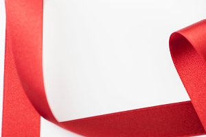 Abstract shapes background of red fabric ribbon on white background. Copy space.