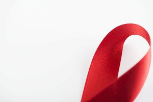 Red fabric ribbon on white background. Abstract. Copy space.
