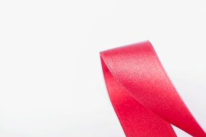 Red fabric ribbon on white background. Copy space.